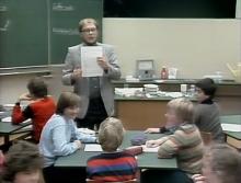 Lehrer hält Aufgabenblatt hoch